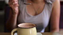 Girl in a cafe drinking coffee or hot chocolate with marshmallow Stock Footage
