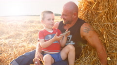 Father and son sitting in a field and play games on mobile phone Stock Footage