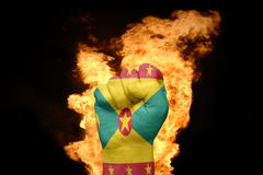 Fire fist with the national flag of grenada Stock Photos