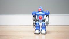 Toy robot walks then falls over onto wooden floor Stock Footage