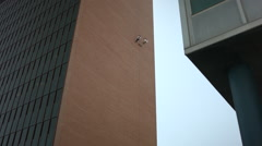 Rappelling Down the side of a Building Stock Footage