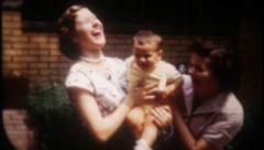 2515 - women laugh out loud as they hold a little boy - vintage film home movie - stock footage