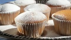 Applying Powdered Sugar To Muffins On Platter In Bakery - stock footage