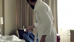 Young businessman preparing clothes for work in hotel room Stock Footage