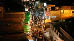 Tilt: People enjoy night bazaar in the alleys of the old city Safed, Israel Stock Footage
