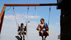 Father and son ride on the swing, swing with an iron chain Stock Footage