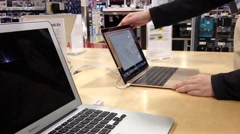 Woman trying new Macbook inside Best buy store - stock footage