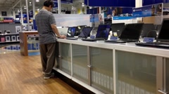People trying new computer inside Best buy store Stock Footage