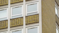 4K Camera panning past rows of windows in a UK high rise apartment block Stock Footage