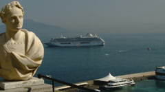 Cruise ship anchored off the coast of Sorrento, Italy with Roman Statue in FG Stock Footage