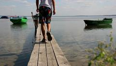 Boy walking on a pier on the shore of the river near the boat and looks Stock Footage