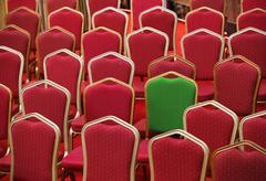 Diversity or unique concept - green chair in a group of red ones - stock photo