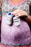 Pregnant woman holding baby shoes - stock photo