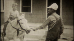 2522 - young boy rides a burro down on the farm - vintage film home movie Stock Footage