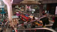 People travel up outdoor escalator, against crowded traffic on road, asian city Stock Footage