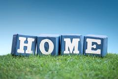 HOME sign made of wooden blocks on a grass - stock photo