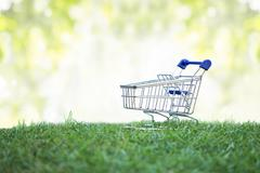 Trolley on green grass, Green Shopping concept - stock photo