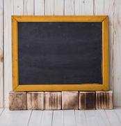 Black chalkboard on wooden background, horizontally placed - stock photo