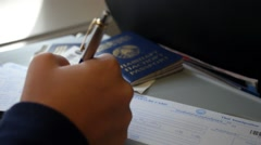 Hand Filling Immigration Form on Flight to Visit Country Stock Footage
