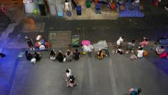People seat on pavement under Siam BTS station, view from above, evening time Stock Footage
