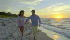 Stock Video Footage of Energetic Young Couple Run Down Beach Together, Holding Hands