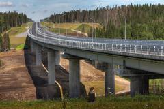 Four-speed road through forest, and steel motor road bridge. - stock photo