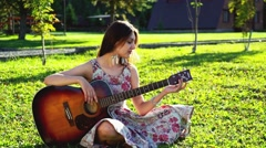 Young beauty girl tune the guitar Stock Footage