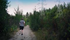 Man Runs On Gravel Path In Forest Near Power Lines Stock Footage