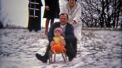 1975: Family dangerously winter snow sledding with young son. Stock Footage