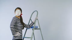 Woman mime standing on a ladder and paint the invisible wall Stock Footage