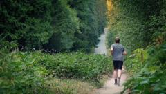 Man Jogs On Dusty Gravel Path Through Sunset Forest Stock Footage