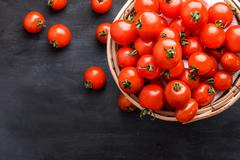 pile of cherry tomatoes in a rattan basket - stock photo