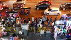 Commuters queue in line, wait bus on lively road side, evening city - stock footage