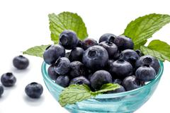 Stock Photo of blueberries and mint leaves in a glass bowl