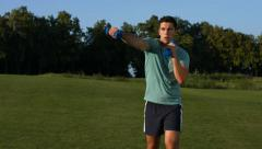 Guy with dumbbells on a lawn. Stock Footage