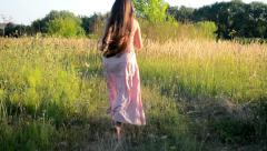 Woman in a pink dress running down the road in a field Stock Footage