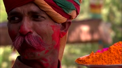 Holi Festival India Man holding dish of coloured powder - stock footage
