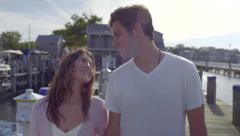 Attractive Couple Hold Hands, Walk Down Dock In Marina (Slow Motion) Stock Footage