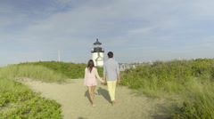 Young Couple Walk (Away From Camera) Toward Lighthouse Stock Footage