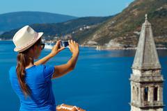 Girl in hat making photos of the smartphone Perast in Boka Kotor Bay, Montene - stock photo