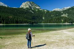 Woman hiker with a backpack and walking stick on the Black Lake in Durmitor N Stock Photos