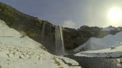 Tourists visiting waterfall Seljalandsfoss in wintertime Stock Footage