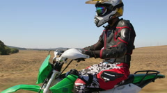 Enduro racer riding his offroad bike on road Stock Footage