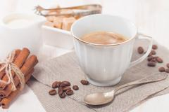 A cup of coffee with milk and sugar - stock photo
