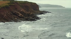 Slow motion shot of a very rocky shore cliffs and the rough ocean water Stock Footage