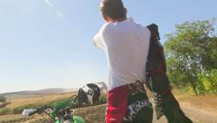 Young enduro racer puts on chest protector beside his dirt bike Stock Footage