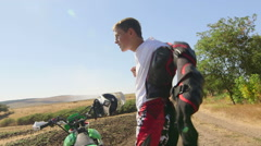 Young enduro racer dressing motorcycle protective gear beside his dirt bike Stock Footage