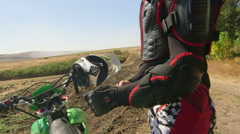 EYoung enduro racer dressing motorcycle protective gear beside his dirt bike Stock Footage