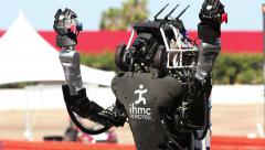 IHMC Robotics' Running Man Atlas Robot Raises its Arms in Triumph Stock Footage