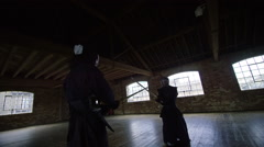 Japanese kendo fighters with bamboo swords competing in dark industrial building Stock Footage